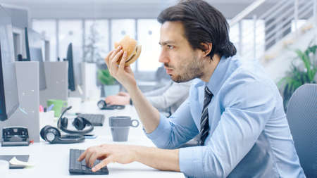 In the Bright Modern Office Young Businessman Eats Hamburger Sitting at His Desktop Computer, He Chewing the Bun and Continues to Work During His Lunch. In the Background Colleagues Working