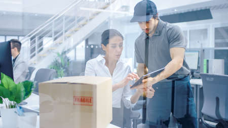 Happy Delivery Man Enters Corporate Office, Hands Package to a Beautiful Businesswoman, She signs Her Signature on the Tablet Computer. Big Bright Modern Business Company Office with Professionals. Stock Photo