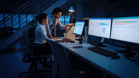 Late at Night In Modern Office: Businessman and Businesswoman Work on Desktop Computer, Having Discussion, Finding Problem Solution, Finishing Project. Successful Dedicated Responsible Office Workers
