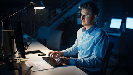 Portrait of Ambitious and Confident Businessman Uses Desktop Computer, Typing on a Keyboard, Monitoring Business Transactions, Signing Contracts. Works Late at Night in Big Corporate Office