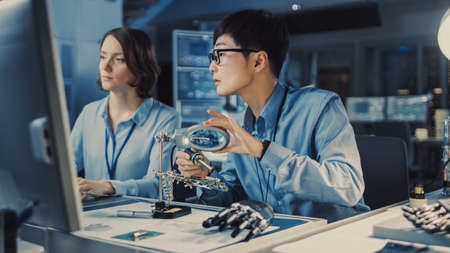 Japanese Development Engineer in Blue Shirt is Soldering a Circuit Board in a High Tech Research Laboratory with Modern Equipment. His Colleague Asks Him a Questio and Points on the Compter Screen. Stock fotó