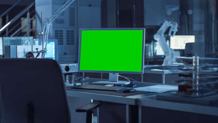 On the Desk Computer with Isolated Green Mock-up Screen Display. In the Background Robot Arm Concept Standing in Heavy the Dark.Industry Engineering Facility Stock fotó - 155444773
