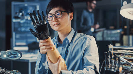 Futuristic Prosthetic Robot Arm Being Tested by a Professional Japanese Development Engineer in a High Tech Research Laboratory with Modern Computer Equipment. He is Satidfied with the Result.