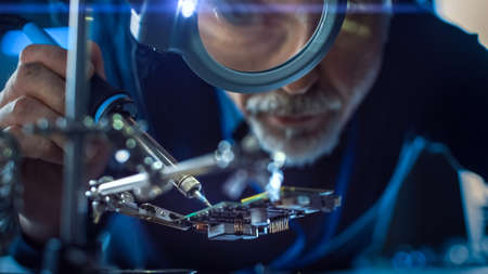 Electronics Maintenance and Repair Engineer Soldering Motherboard, Microchip and Circuit Board, Looking through Magnifying Glass. Conceptual Shot: Close-up Low Angle Magnifying Eye and Face