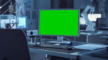 On the Desk Computer with Isolated Green Mock-up Screen Display. In the Background Robot Arm Concept Standing in Heavy the Dark.Industry Engineering Facility Stock fotó