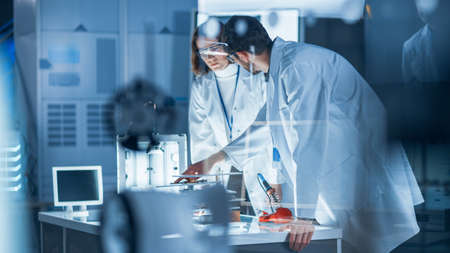 Diverse International Team of Industrial Scientists and Engineers Wearing White Coats Working on Heavy Machinery Design in Research Laboratory. Professionals Using 3D Printer, Computers and Microscope