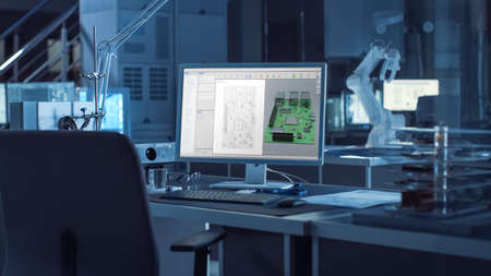 On the Desk Computer With CAD Software and Design of 3D Industrial Machinery Component. In the Background Robot Arm Concept Standing in Heavy Dark. Industry Engineering Facility.