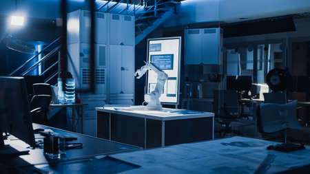 In Industrial Robot Desing Research Laboratory: Robotic Arm Prototype Standing Illuminated on the Desk. In the Dark Background Various High Tech Devices, Computers, Digital Whiteboard and Blueprints Stock fotó - 155446445