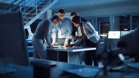 Diverse Team of Electronics Development Engineers Standing at the Desk Working with Documents, Solving Project Problems Late at Night. Specialists Working on Ultra Modern Industrial Design. Stock fotó - 155446198