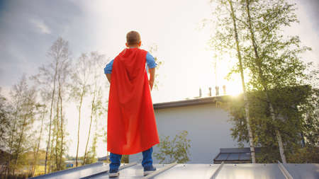 Boy is Playing a Role of a Super Hero. Hes Standing on a Roof of a House with His Hands on His Waist. Young Man is Wearing a Bright Red Cape. Hes Looking at the Sun.