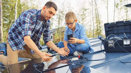 Father and Son Installing Solar Panels to a Metal Basis. They Work with Wiring on a House Roof on a Sunny Day. Boy is Looking at a Manual on a Smartphone. Father Connects the Plugs.