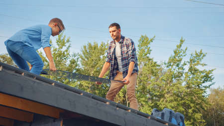 Father and Son Installing Solar Panels to a Metal Basis. They are Holding the Panels on a House Roof on a Sunny Day. Concept of Ecological Renewable Energy at Home and Quality Family Time. Banco de Imagens