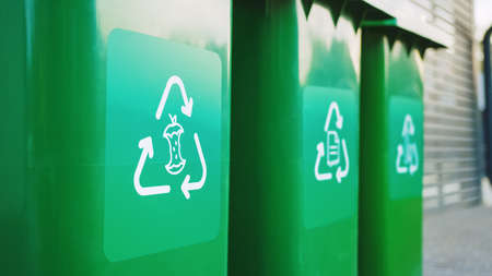 Green colored, plastic garbage bins, with different recycle logos on front, stacked in row against brown wood wall. Concept of waste sorting for food, paper and bottles. Saving Environment from Trash. Banco de Imagens