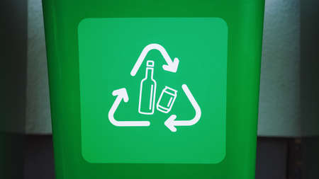 Close-up Shot of a Green colored, plastic garbage bin, with bottle recycle logos on front. Concept of waste sorting for bottles. Saving Environment from Trash.
