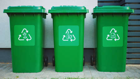 Green colored, plastic garbage bins, with different recycle logos on front, stacked in row against brown wood wall. Concept of waste sorting for food, paper and bottles. Saving Environment from Trash. Banque d'images