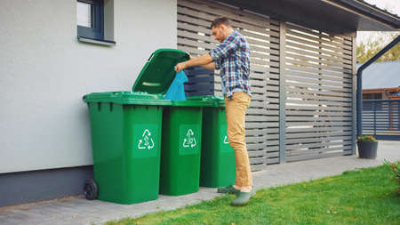 Caucasian Man is Throwing Away Plastic Bags with Sorted Trash. Concept of waste sorting for food, paper and bottles. Saving Environment from Trash. Archivio Fotografico
