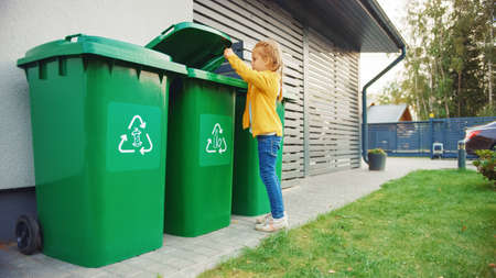 Young Girl is Throwing Away an Empty Plastic Bottle into a Trash Bin. She Uses Correct Garbge Bin Because This Family is Sorting Waste and Helping to Save the Environment. Banco de Imagens