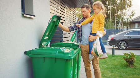 Father Holding a Young Girl and Throw Away an Empty Bottle and Food Waste into the Trash. They Use Correct Garbage Bins Because This Family is Sorting Waste and Helping the Environment.