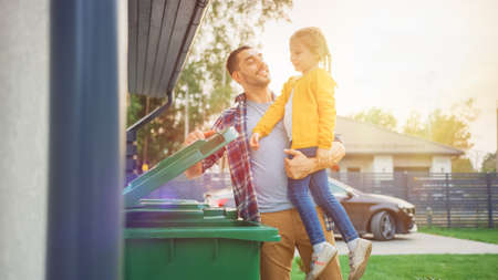 Happy Father Holding a Young Girl and Threw Away a Food Waste into the Trash. They Use Correct Garbage Bins Because This Family is Sorting Waste and Helping the Environment.