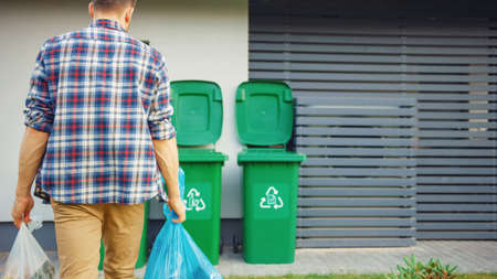 Caucasian Man is Walking Outside His House in Order to Take Out Two Plastic Bags of Trash. One Garbage Bag is Sorted with Biological Food Waste, Other with Recyclable Bottles Garbage Bin.