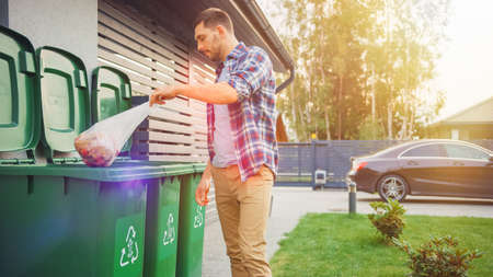 Caucasian Man is Throwing Away Two Plastic Bags of Trash next to His House. One Garbage Bag is Sorted with Biological Food Waste, Other with Recyclable Bottles Garbage Bin. Banque d'images