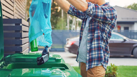 Caucasian Man in Checkered Shirt is Throwing Away Bottles from a Plastic Bag into the Trash Bin. He Uses Correct Garbage Bin Because This Family is Sorting Waste and Helping the Environment.