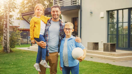 Portrait of a Happy Family of Three: Father, Daughter, Son. They Are Posing In Front of Camera on a Lawn Next to Their Country House and Smile. Dad is Holding the Girl in His Arms, Boy - Football. Banco de Imagens