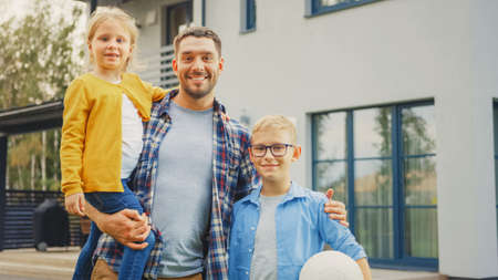 Portrait of a Happy Family of Three: Father, Daughter, Son. They Are Posing In Front of Camera on a Lawn Next to Their Country House. Dad is Holding the Girl in His Arms. Boy is Holding a Football.