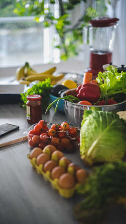 Close up Shot of a Fresh Vegetables Lying on a Table: Cherry Tomatoes, Green Salad, Cabbage, Papper. Authentic Stylish Kitchen with Healthy Food. Natural Clean Products from Organic Farming.