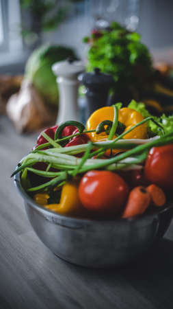 Close up Shot of a Gray Bowl Full of Fresh Healthy Vegetables Standing on a Kitchen Table. Natural Clean Products Prepared for Salad: Yellow Sweet Paper, Red Tomatoes, Green Onion, Carrot.