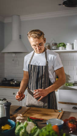 Handsome Man in White Shirt and Apron is Making a Healthy Organic Salad Meal in a Modern Sunny Kitchen. Hipster Man in Glasses Cooking. Natural Clean Diet and Healthy Way of Life Concept.