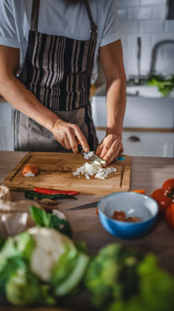 Handsome Man Chopping a Green Spring Onion with a Sharp Kitchen Knife. Man in White Shirt and Apron is Making a Organic Salad Meal in a Modern Sunny Kitchen. Natural Clean Diet and Healthy Lifestyle. Banco de Imagens
