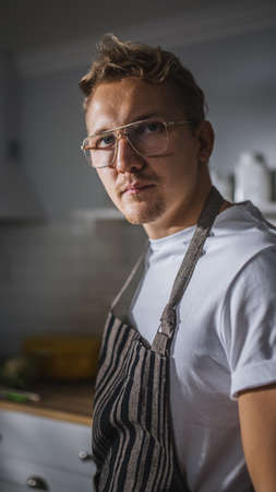Portrait Shot of a Handsome Cook in White Shirt and Apron Posing on Camera in a Bright Modern Kitchen. Hipster Man in Glasses. Natural Clean Diet, Healthy Way of Life Concept
