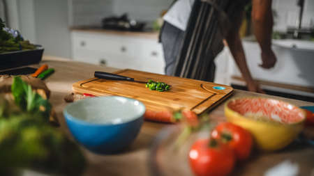 Close Up Shot of a Chopped a Green Spring Onion on a Cutting Board. Healthy Organic Salad Meal in a Modern Kitchen. Natural Clean Diet and Healthy Way of Life Concept. Banco de Imagens