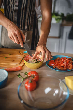 Close up Shot of a Hipster Man Preparing a Healthy Organic Salad Meal in a Modern Kitchn. Natural Vegetarian Diet and Healthy Way of Life Concept.