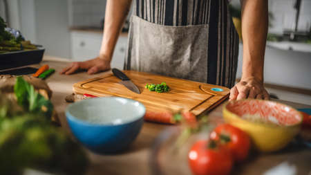 Close Up Shot of a Man and a Chopped Green Spring Onion on a Cutting Board. Preparing a Healthy Organic Salad Meal in a Modern Kitchen. Natural Clean Diet and Healthy Way of Life Concept.