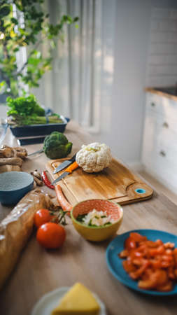 Shot of a Kitchen Table with Vegetables and Cauliflower on a Cutting Board. Healthy Organic Green Food in a Modern Sunny Kitchen. Natural Clean Diet and Healthy Way of Life Concept.