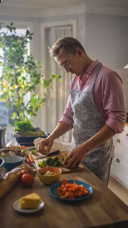 Handsome Man in Pink Shirt and Apron is Making a Healthy Organic Salad Meal in a Modern Sunny Kitchen. Hipster Man in Glasses. Natural Clean Diet and Healthy Way of Life Concept.