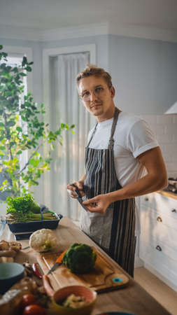 Handsome Man in White Shirt and Apron is Making a Healthy Organic Salad Meal in a Modern Sunny Kitchen. Hipster Man in Glasses Smiles at the Camera. Natural Clean Diet and Healthy Way of Life Concept.