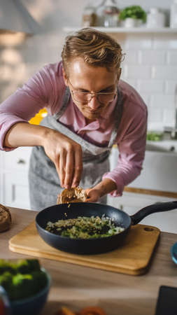 Handsome Young Man Preparing a Healthy Vegetarian Meal on a Frying Pan. Sprinkling Healthy Green Food with Herbs and Spices in a Modern Kitchen. Natural Clean Diet and Healthy Way of Life Concept. Banco de Imagens