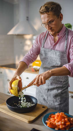 Handsome Man in Pink Shirt and Apron is Preparing a Healthy Vegetarian Meal on a Frying Pan. Healthy Organic Meal in a Modern Sunny Kitchen. Natural Clean Diet and Healthy Way of Life Concept. Banco de Imagens