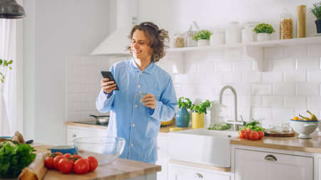 Happy Young Man with Long Hair is Using Smartphone in a Kitchen while Wearing Blue Pajamas. He is Scrolling Social Meadia and News Feed. Energetic Man Drinking Coffee and Having a Healthy Breakfast. Banco de Imagens