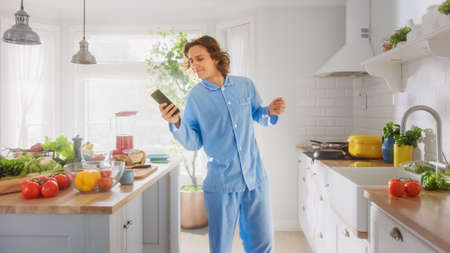 Happy Young Man with Long Hair is Using Smartphone in a Kitchen while Wearing Blue Pajamas. He is Scrolling Social Meadia and News Feed. Energetic Man Having a Healthy Breakfast.