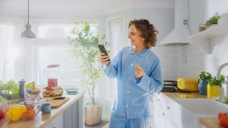 Happy Young Man with Long Hair is Using Smartphone at Home while Wearing Blue Pajamas. Energetic Man Scrolling News Feed and Checking Social Media Notifications. Banco de Imagens