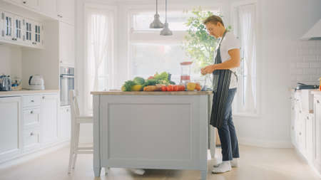 Hipster Young Man in Glasses Cooking on a Modern Kitchen. He Wears an Apron and Preparing a Vegetable Salad in a Sunny Bright Kitchen with Healthy Green Vegetables on a Table.