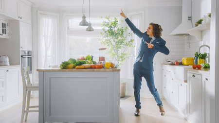 Energetic Funny Young Man with Long Hair Dancing in the Kitchen while Wearing Blue Suit. Bright White Modern Kitchen Area with Healthy Green Vegetables on a Table. Cozy Home.