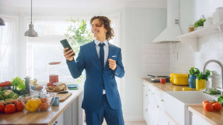 Happy Young Man with Long Hair is Using Smartphone at Home while Wearing Blue Business Suit. He is Listening to Music on a Mobile. Scrolling Social Media Feed in a Kitchen with Healthy Vegetables.