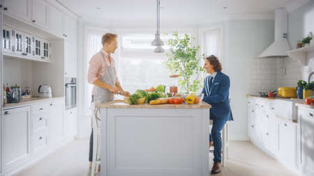 Two Young Handsome Men Talk in the Kitchen. One is Dressed Casually and His Friend Wears a Business Suit. Sunny Modern Kitchen with Healthy Green Vegetables on Table. Happy  Gay Couple at Home.