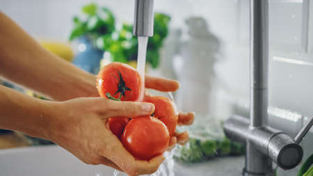 Close Up Shot of a Man Washing Tomatoes with Tap Water. Authentic Stylish Kitchen with Healthy Vegetables. Natural Clean Products from Organic Farming Washed by Hand.