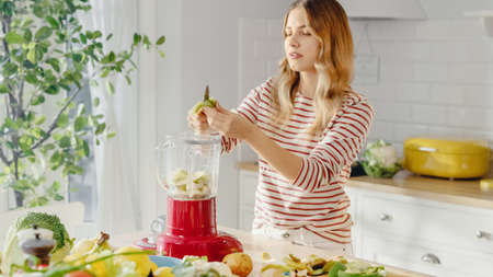 Beautiful Young Female Cutting a Kiwi into a Blender with a Sharp Kitchen Knife. Authentic Stylish Kitchen with Healthy Vegetables. Natural Clean Products from Organic Farming Used to Make Smoothie.